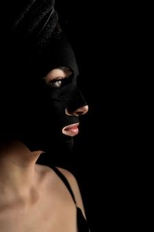 黒い顔のマスクを適用する美しい女性。美容トリートメント。スパの女の子のクローズアップの肖像画は黒い背景に粘土の顔のマスクを適用します。