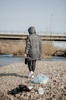 ビーチからプラスチックのゴミを収集し、それをリサイクルのために黒いビニール袋に入れる若い女性。クリーニングとリサイクルのコンセプト。