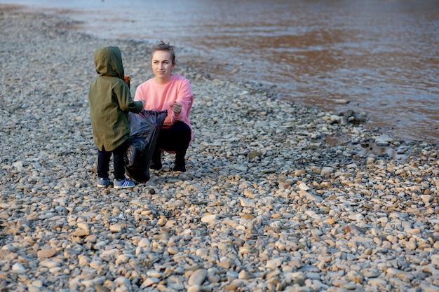 Молодая женщина с сыном собирает пластиковый мусор в мусорный мешок на реке. пустые использованные грязные пластиковые бутылки. загрязнение окружающей среды берега