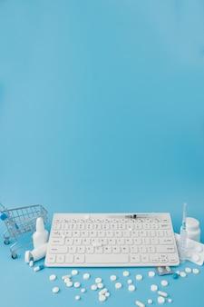 医薬品とキーボードを備えたショッピングカートのおもちゃ。錠剤、ブリスターパック、医療用ボトル、温度計、青色の背景に防護マスク。あなたのテキストのための場所のトップビュー