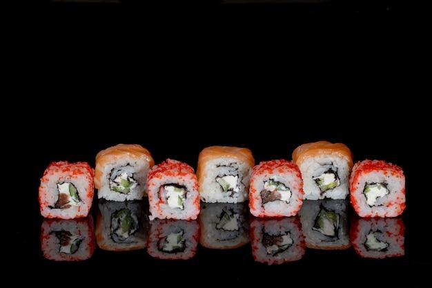 フィラデルフィアは、反射と黒の背景にサーモン、チーズ、キュウリとロールします。寿司フィラデルフィア