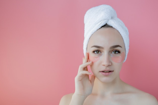 ピンクの背景にアイパッチを持つ美容女性の肖像画。目の下のマスクを持つ女性美容顔。コピースペースを持つスキンケア、化粧品のコンセプト