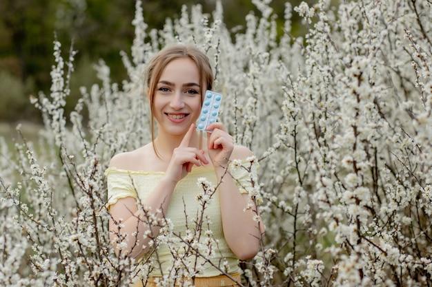 手に薬を持つ女性春のアレルギー屋外の戦い-季節の花に囲まれたアレルギーの女性の肖像画