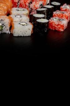 黒いスレートの背景に寿司ロールのセット食品魚フィラデルフィア日本のサーモンおいしい寿司米キュウリ食事伝統的なわさび新鮮な健康的なグルメ生料理