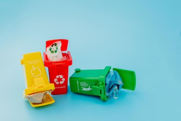 青の背景にリサイクルマークの付いた黄色、緑、赤のごみ箱。街を整頓し、リサイクルのシンボルを残します。自然保護のコンセプト