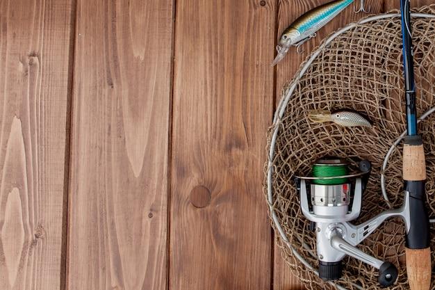釣り道具-スピニング、フック、コピースペースを持つ木製の背景にルアー