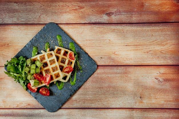 Свежие запеченные бельгийские вафли с рукколой, помидорами и авокадо на черной тарелке. пикантные вафли. концепция завтрака. здоровый завтрак