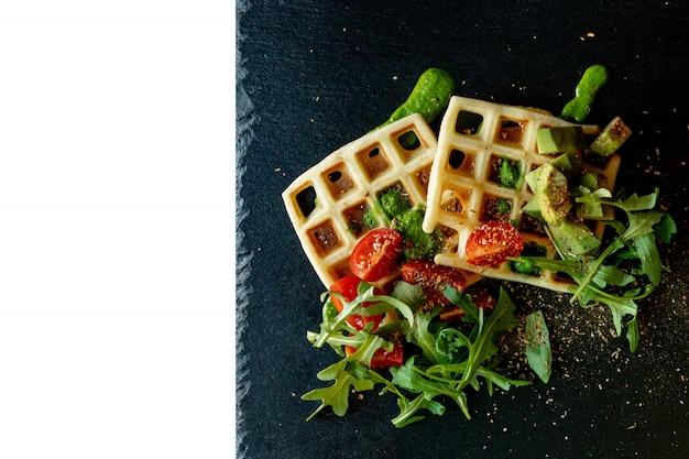 Свежие испеченные бельгийские вафли с рукколой, томатами и авокадоом на черноте плита изолированная на белой предпосылке. пикантные вафли. концепция завтрака. здоровый завтрак