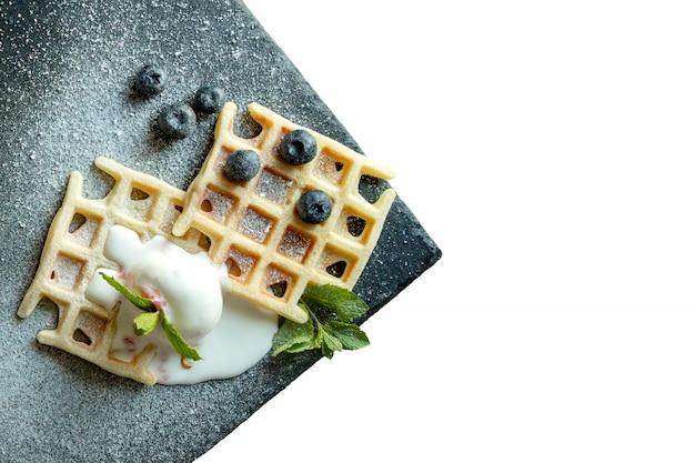 焼きたての自家製クラシックベルギーワッフルにアイスクリーム、新鮮なブルーベリー、白い背景に、トップダウンビューで分離されたミントをトッピング。おいしいワッフル。朝食のコンセプト