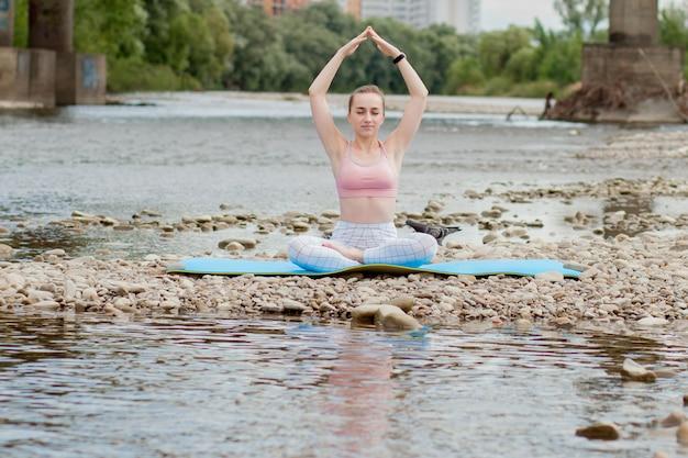 Здоровая девушка расслабляется во время медитации и делает упражнения йоги в красивой природе на берегу реки