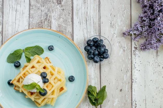 焼きたての自家製クラシックベルギーワッフルにアイスクリーム、新鮮なブルーベリー、木製の背景にミントをトッピング。おいしいワッフル。朝食のコンセプト
