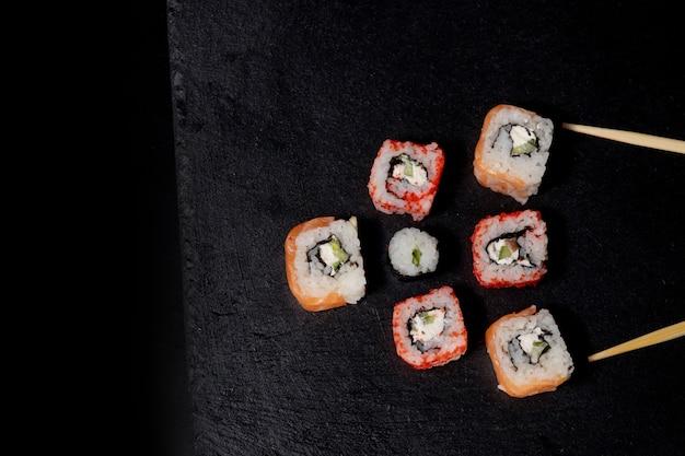 フィラデルフィアは、黒の背景にサーモン、チーズ、キュウリとロールします。寿司フィラデルフィア