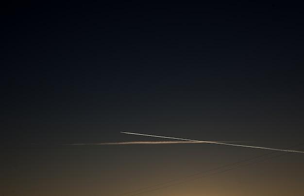夕焼け空の飛行機。飛行機は日没で空に