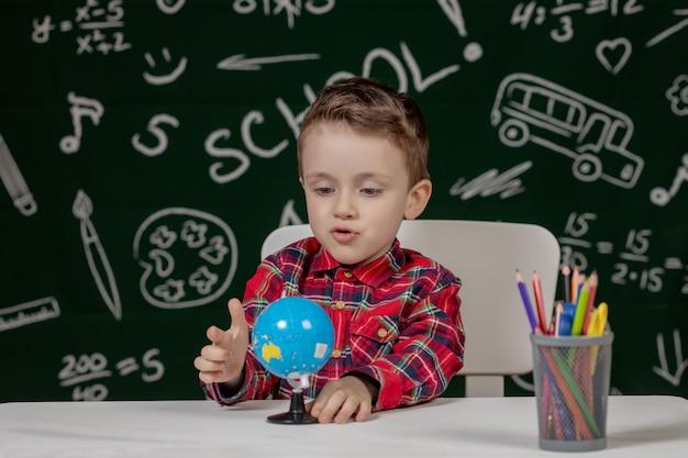 黒板に小さな地球を手で保持しているかわいい男の子の肖像画。学校の準備ができています。学校に戻る。