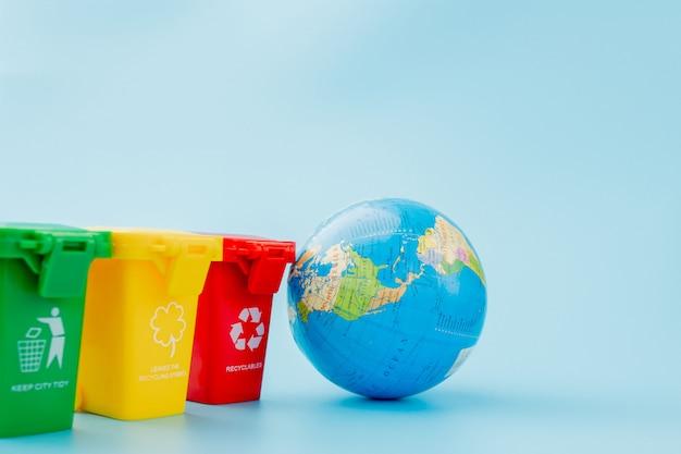 青い表面にリサイクルマークが付いた黄色、緑、赤のごみ箱。街を整頓し、リサイクルのシンボルを残します。自然保護の概念
