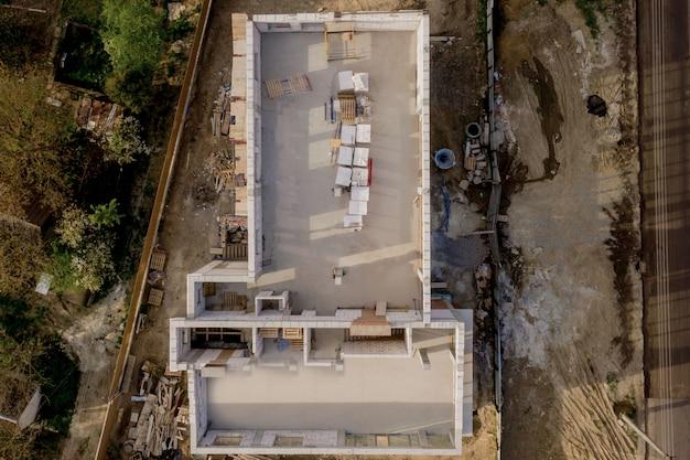 白い発泡コンクリートブロックで作られた建設中の家の建築現場。家の新しいフレームを構築する