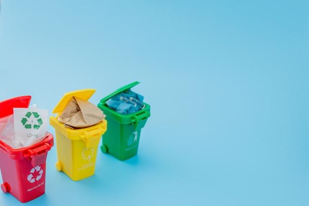 青色の背景にリサイクルマークの付いた別のごみ箱