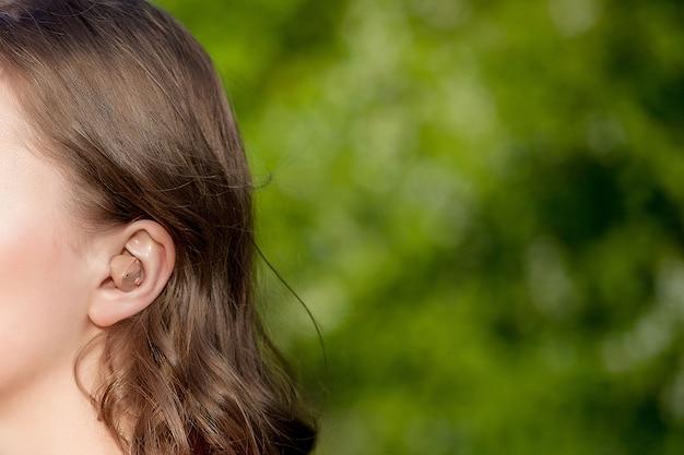 耳に補聴器を持つ女性