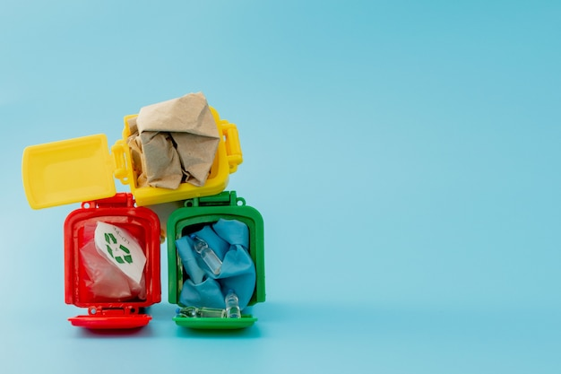青の背景にリサイクルマークの付いた黄色、緑、赤のごみ箱。街を整頓し、リサイクルのシンボルを残します。自然保護の概念