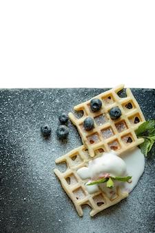 焼きたての自家製クラシックベルギーワッフルにアイスクリーム、新鮮なブルーベリー、ミントをトッピング。トップダウンビュー。おいしいワッフル。朝食のコンセプト