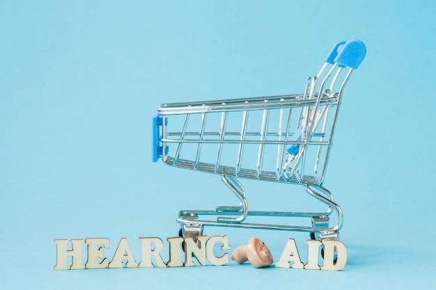 青色の背景に補聴器。医療、薬局、ヘルスケアの概念。