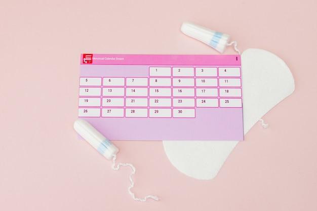 タンポン、フェミニン、生理用生理用ナプキン、フェミニンカレンダー、ピンクの背景で生理中の痛み薬。月経周期と排卵の追跡