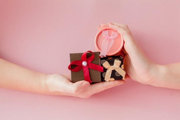ピンクの背景の女性の手の中の小さなギフトボックス。バレンタインデー、母の日、誕生日のお祝いコンセプト