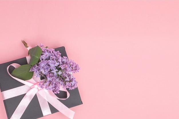 ライラックで飾られたピンクの背景にピンクのリボン付きギフトボックス。母の日。誕生日バレンタインデー。コピースペース