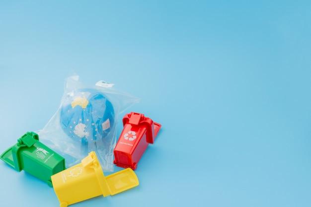 青の背景にリサイクルマークの付いた黄色、緑、赤のごみ箱。