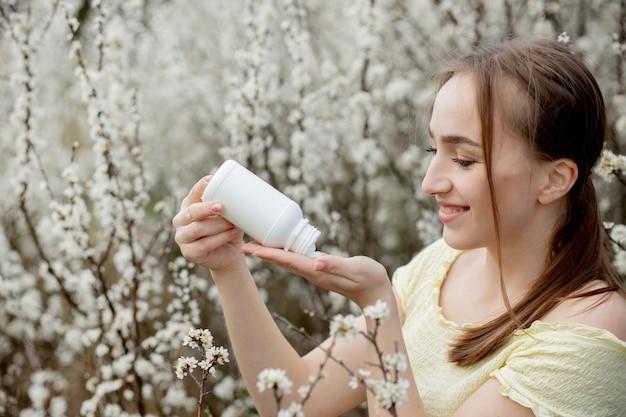 Женщина с лекарством в руках борьба с весенней аллергией на улице - портрет женщины с аллергией в окружении сезонных цветов