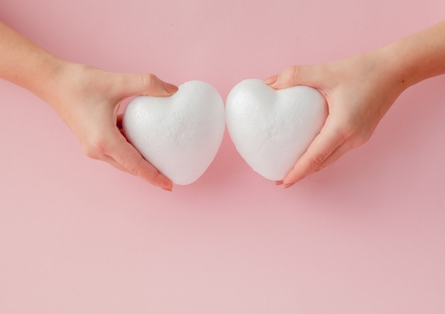 Белые пустые любовные сердечки в руках