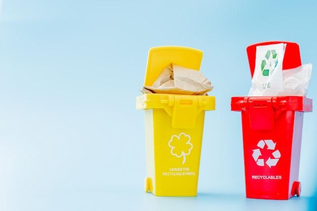 水色の壁にリサイクルマークが付いた黄色、緑、赤のごみ箱。街を整頓し、リサイクルのシンボルを残します。自然保護の概念