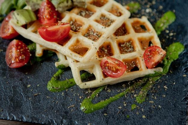 Свежие испеченные бельгийские вафли с рукколой, помидорами и авокадо на черной тарелке. пикантные вафли. концепция завтрака. здоровый завтрак