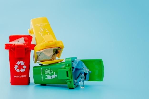 青の背景にリサイクルマークが付いた黄色、緑、赤のごみ箱。街を整頓し、リサイクルのシンボルを残します。自然保護の概念