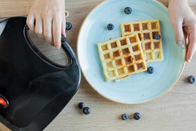 ワッフルメーカーで焼き上げるワッフル。おいしいワッフル。朝食のコンセプト