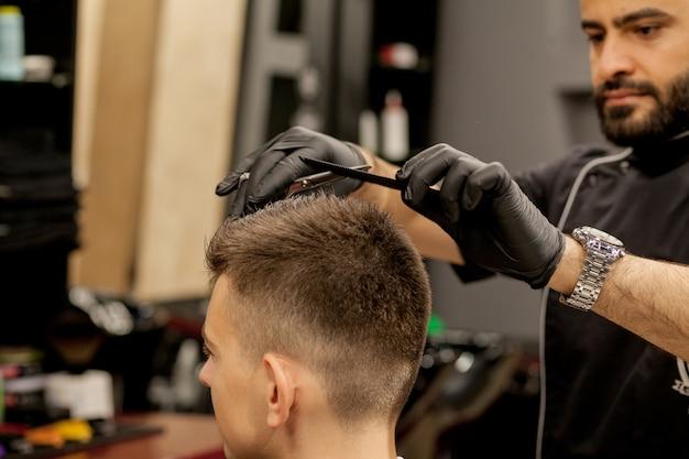 Брутальный парень в современной парикмахерской. парикмахер делает прическу мужчине