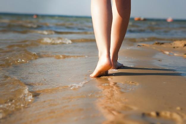 Женщина гуляя на пляж оставляя следы в песке