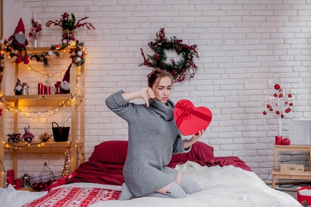 Женщина в сером свитере с красной подарочной коробкой