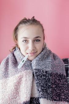 Грипп простуды. женщина, имеющая высокую температуру. больная девушка с лихорадкой проверяя ртутный термометр на розовой стене.
