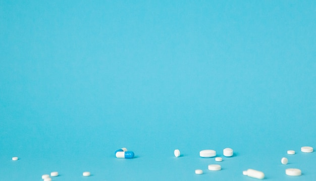 青い壁の上の各種医薬品錠剤、錠剤、カプセル