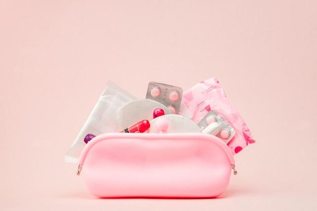 女性の親密な衛生用品-ピンクの壁の衛生パッドとタンポン、コピースペース。月経の概念。トップビュー、フラットレイアウト、コピースペース