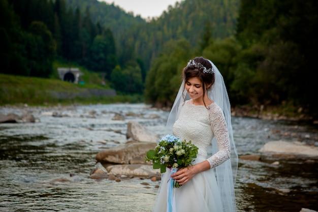 Счастливые молодожены стоя и улыбаясь на реке. молодоженов, фото на день святого валентина