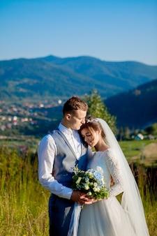 Молодожены улыбаются и обнимают друг друга среди поляны на вершине горы. свадебная прогулка в лесу, в горах, нежные эмоции пары, фото на день святого валентина
