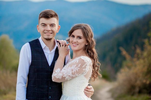 Красивая свадьба пара, жених и невеста, в любви на стене гор. жених в красивом костюме и невеста в белом роскошном платье. свадебная пара гуляет