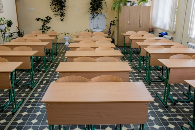 貧しい学校の教室で古い木製の列講義椅子