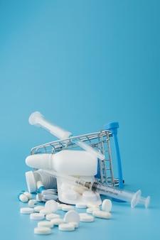 Разбросанные разнообразные таблетки, спай, бутылки, термометр, шприц и пустая тележка для покупок