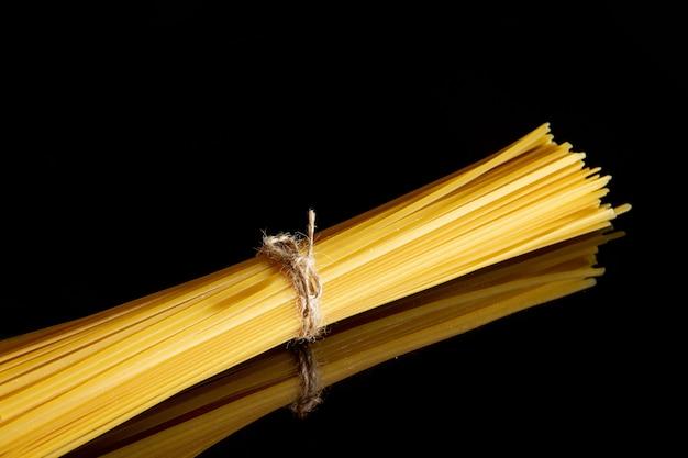 Сухие спагетти стоит на черном фоне. концепция приготовления пищи. пространство для текста.