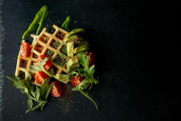 ルッコラ、トマト、黒皿にアボカドの焼きたてベルギーワッフル。おいしいワッフル。朝食のコンセプトです。ヘルシーな朝食