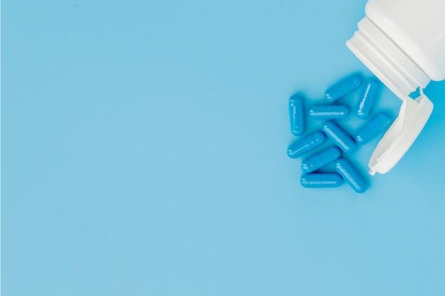 青いカプセル、青い背景に錠剤。白い瓶にカプセル。ビタミン、女性の健康のための栄養補助食品