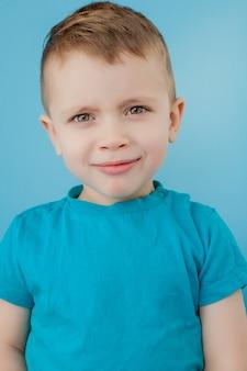 Портрет милый маленький мальчик с стильные вьющиеся прически в голубой футболке стоя, глядя на камеру с серьезным внимательным лицом, спокойное задумчивое выражение.